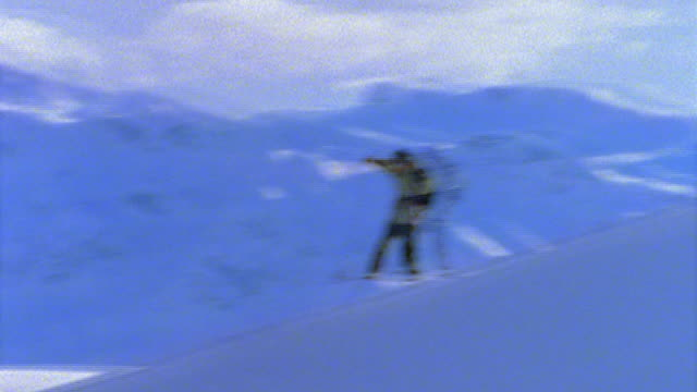 slow motion PAN snowboarder jumping over ridge + wiping out / snow covered mountains in background