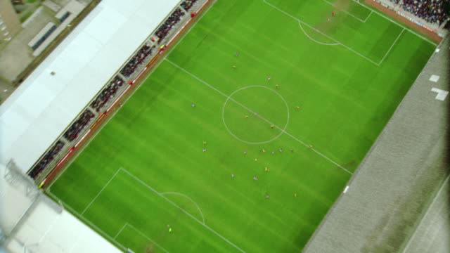 AERIAL slow motion soccer stadium during game / zoom in + zoom out of field / West Ham FC, London