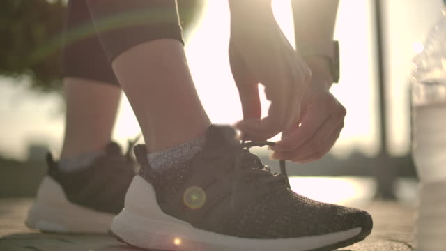 slow motion sport woman tying shoelaces - tied up stock videos & royalty-free footage