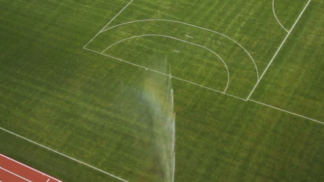 vídeos de stock, filmes e b-roll de slow motion sprinkler system over athletic field, stadium - munich, germany - aspersor