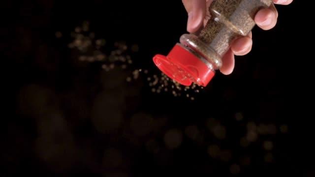 slow motion: sprinkling black pepper flake on top of camera view. - seasoning stock videos & royalty-free footage