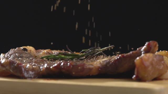 vídeos de stock e filmes b-roll de slow motion sprinkling black pepper to steak beef. - pimenta do reino
