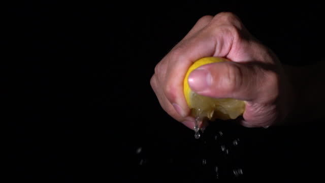 slow motion squeeze lemon by hand palm and fade out - lemon stock videos & royalty-free footage