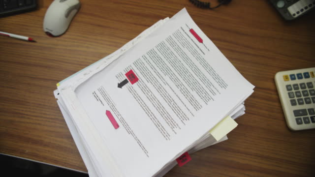 Slow motion stack of paperwork is dropped on an office desk and bounces on impact.