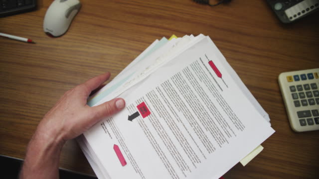 Slow motion stack of paperwork is dropped on an office desk.