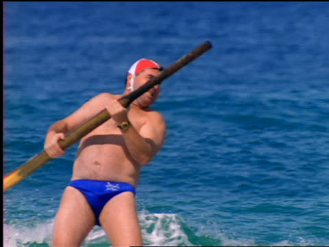 slow motion standing male lifeguard steering small boat with oar / bondi beach, australia - 1999 stock videos & royalty-free footage