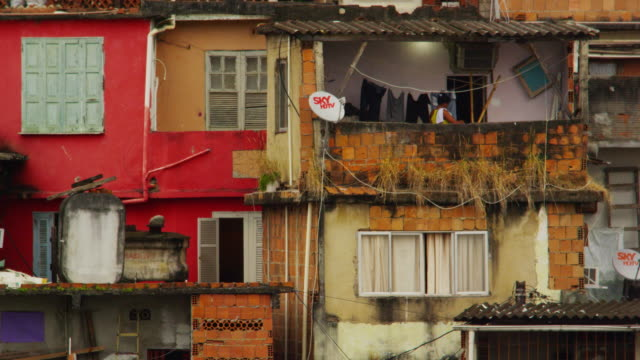 vídeos de stock, filmes e b-roll de slow motion static footage of a colorful, run-down favela and a woman - com fome