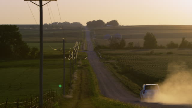 slow motion static view of car driving down dirt road. - nebraska stock-videos und b-roll-filmmaterial