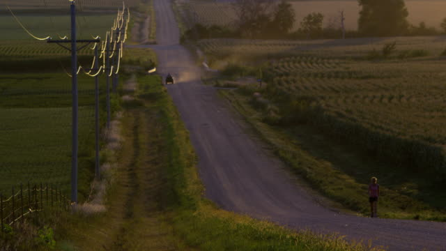 Slow motion static view of woman walking up dirt road.