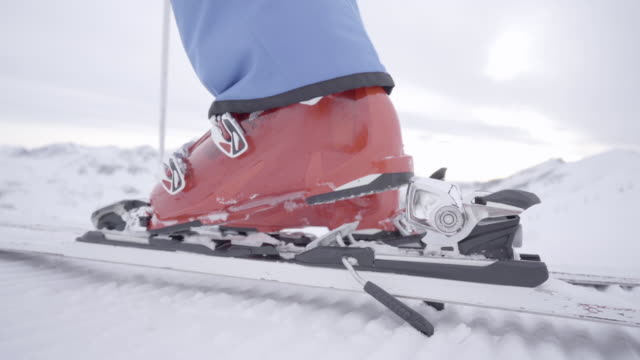 slow motion stepping in ski binding close up