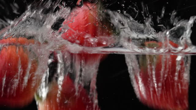 slow motion : strawberry falling into a water - fruit bowl stock videos & royalty-free footage