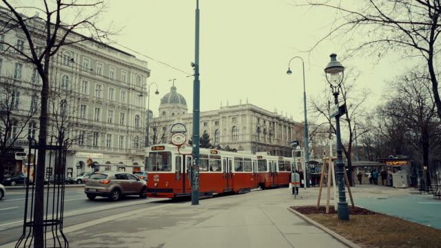 zeitlupenstraßen wien, österreich während der wintertage mit verkehrsstrom, straßenbahn und menschen, die herumlaufen - tram stock-videos und b-roll-filmmaterial