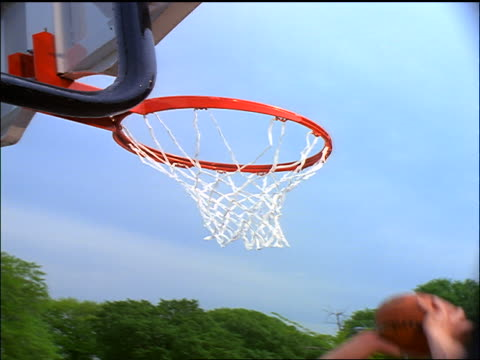 slow motion STRETCHED close up man slam dunking basketball as other man tries to block him outdoors
