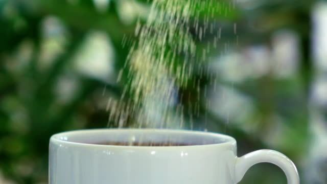 slow motion strews sugar to mug - sprinkling stock videos & royalty-free footage