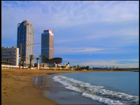 slow motion surf rolling onto beach near hotel arts + torre mapfe / barcelona, spain - 10秒或更長 個影片檔及 b 捲影像
