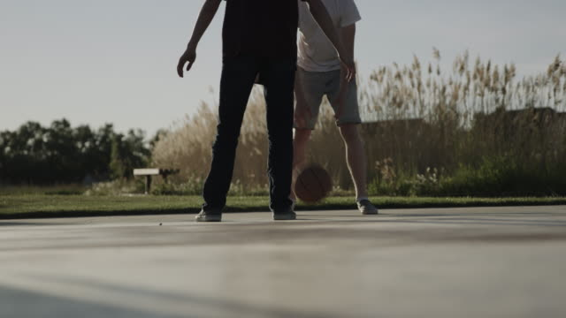 vídeos de stock e filmes b-roll de slow motion surface level view of boys playing basketball on court / lehi, utah, united states - lehi