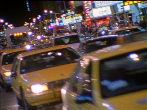 slow motion pan taxis + traffic coming towards camera in times square at night / new york city - 1998 stock videos & royalty-free footage