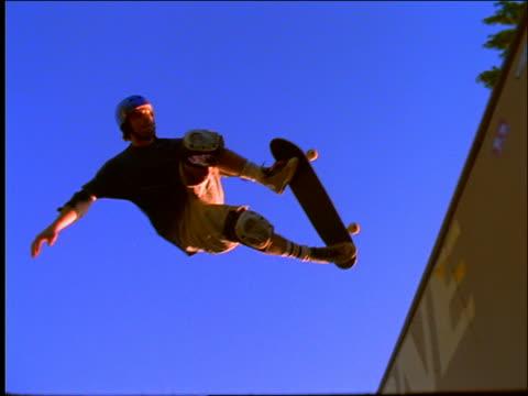 slow motion teen boy skateboarding on ramp