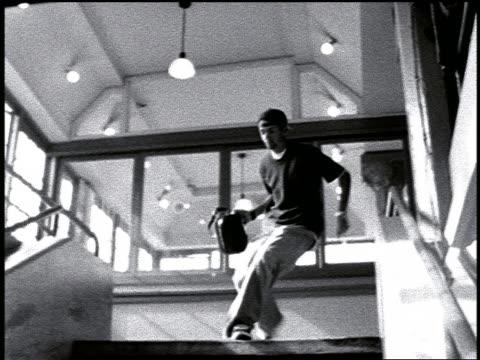 vídeos y material grabado en eventos de stock de b/w slow motion pan teen purse snatcher running down flight of stairs in building - un solo adolescente