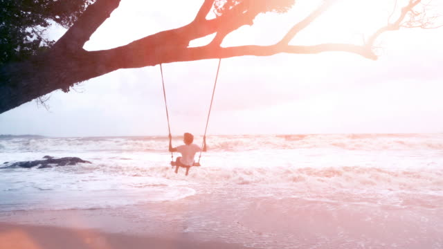 WS Slow Motion, Teenage boy swinging on a swing near the sea.