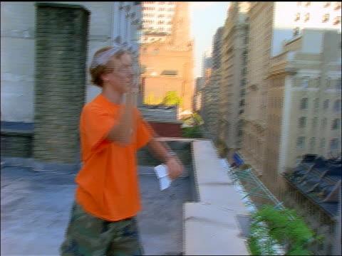 stockvideo's en b-roll-footage met slow motion pan teenage boy throwing paper airplane off of nyc roof - alleen één tienerjongen