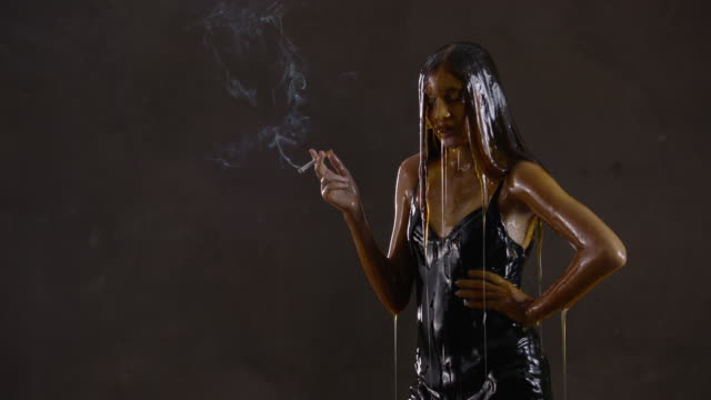 Slow motion, teenage girl covered in honey smokes cigarette
