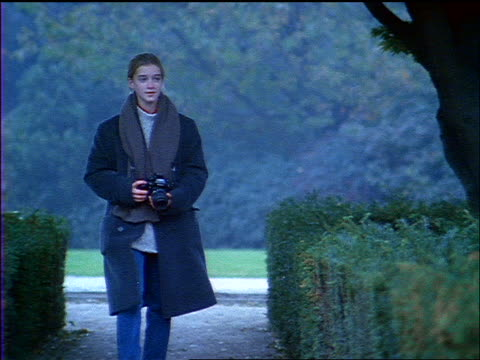 blue slow motion teenage girl in overcoat walking through park taking photographs - 1998点の映像素材/bロール