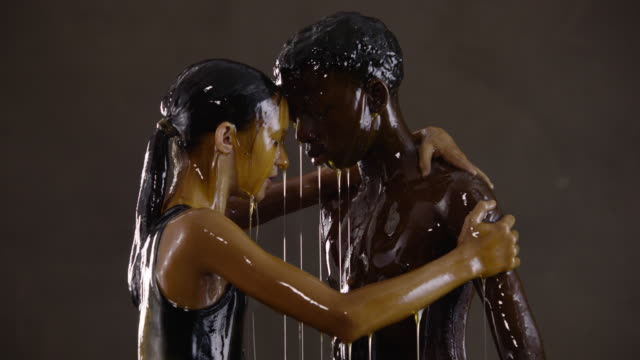 slow motion, teenagers covered in honey hug each other - nackter oberkörper stock-videos und b-roll-filmmaterial