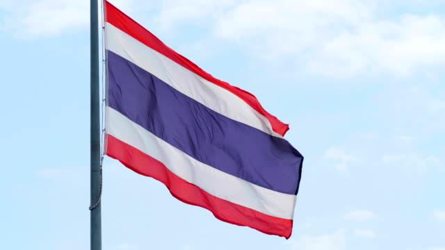 vídeos de stock e filmes b-roll de slow motion thai flag with blue sky background. - cultura tailandesa