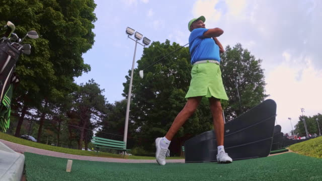 slow motion: the active, optimistic 77-years-old senior black woman playing golf - senior golf swing stock videos & royalty-free footage