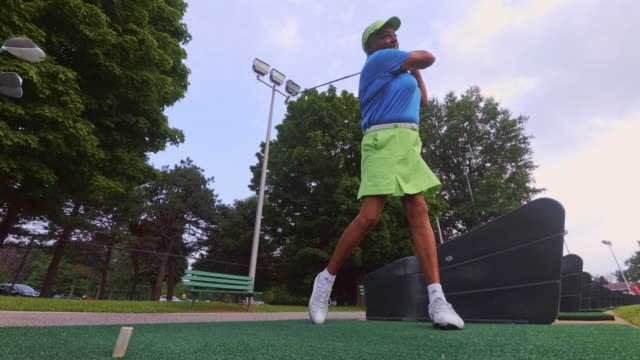 slow motion: the active, optimistic 77-years-old senior black woman playing golf - golfer stock videos and b-roll footage