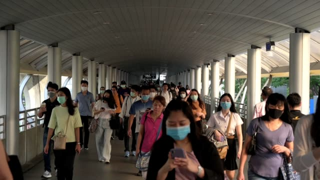 slow motion. the crowd is wearing protective masks prevent coronavirus, covid 19 virus during virus outbreak and pm2.5 air pollution crisis rush hour bangkok, thailand. - epidemic stock-videos und b-roll-filmmaterial