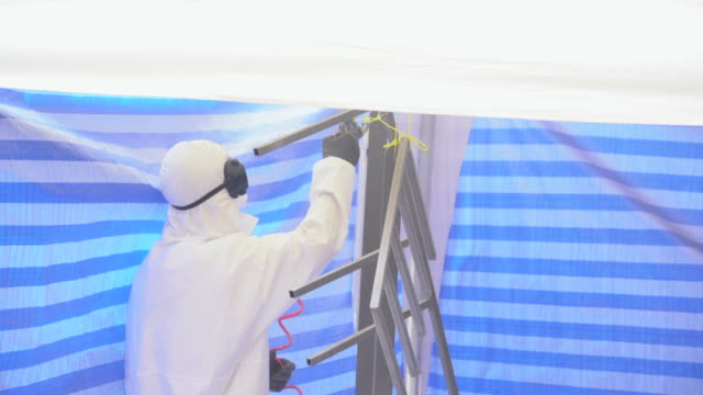 slow motion: the mature man wearing protective mask and coveralls painting the furniture - airbrush stock videos & royalty-free footage
