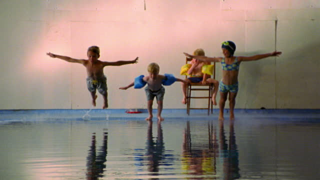 slow motion three children jumping into indoor pool while young boy in swimsuit on chair watches - diving into water stock videos & royalty-free footage