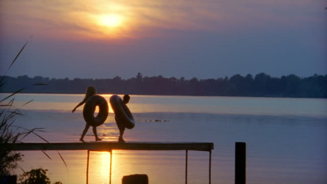 slow motion three children with inner tubes jumping off end of pier into lake at sunset - badeanzug stock-videos und b-roll-filmmaterial