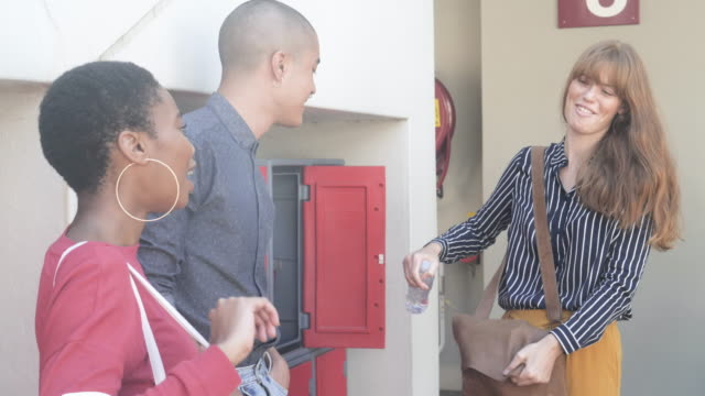 slow motion, three college students talk at locker - locker stock videos & royalty-free footage