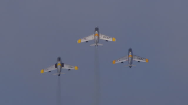 slow motion three f-86 sabre military air force jet planes perform loop-the-loop in tight formation at an air show and disappear in the clouds. - acrobatica aerea video stock e b–roll