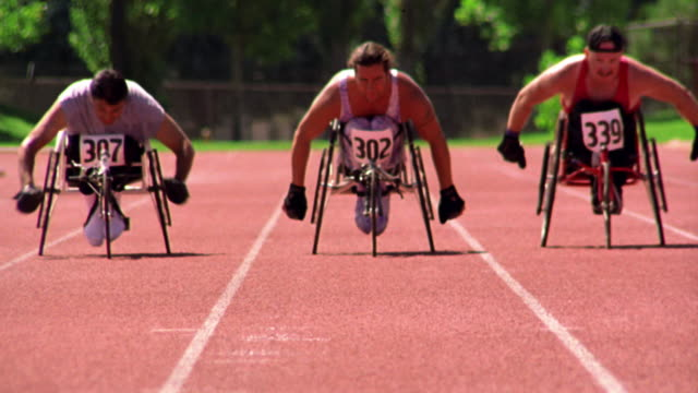 slow motion three men in wheelchairs racing toward camera on track - 車いす点の映像素材/bロール