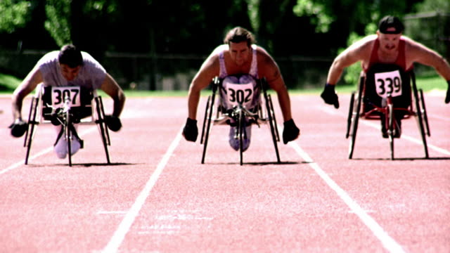 overexposed selective focus slow motion three men in wheelchairs racing toward camera on track - wheelchair stock videos and b-roll footage