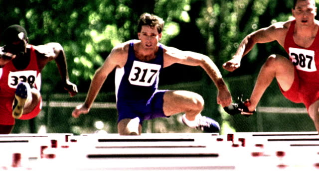 overexposed selective focus slow motion three men jumping hurdles in race on track - spandex stock videos & royalty-free footage