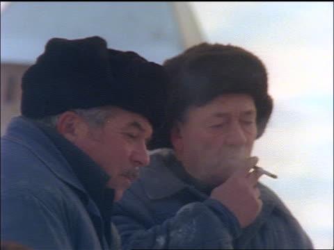 vídeos y material grabado en eventos de stock de slow motion pan three middle aged russian men in fur hats smoking cigarettes - ruso europeo oriental
