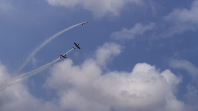 Slow motion three Soviet Yak-52 vintage prop airplanes perform aerobatics in tight formation at an air show.