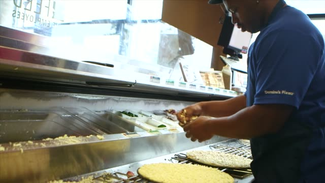 a slow motion tight shot of a dominos pizza employee grabbing cheese from a bin and spreading it on a pizza in ann arbor michigan on october 9 a... - posizionare video stock e b–roll