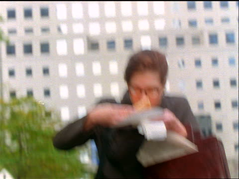 slow motion tilt down close up businesswoman with eyeglasses eating slice of pizza + hurrying towards camera outdoors - take away food stock videos and b-roll footage