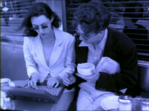B/W BLUE slow motion tilt down couple sitting in outdoor cafe using laptop computer / man holding coffee cup