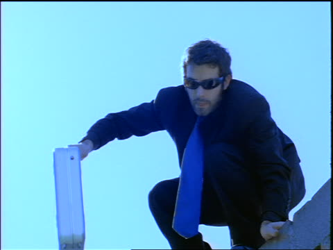 BLUE slow motion tilt down man in sunglasses with metal briefcase jumping off of concrete wall