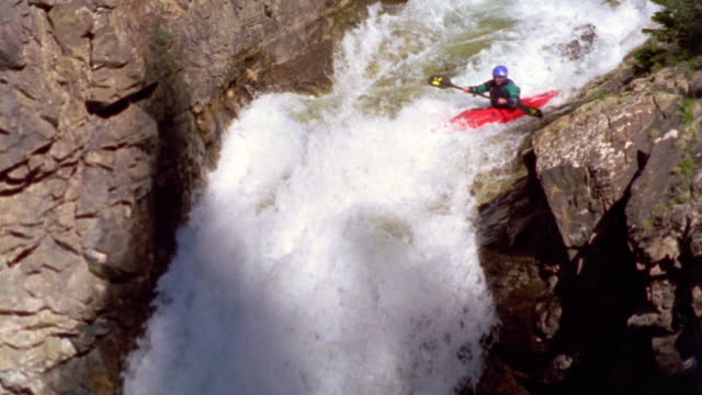 slow motion tilt down man kayaking over waterfall in rapids + disappearing under water