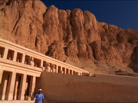 slow motion tilt down man walks past camera from temple at foot of cliff / temple of queen hatshepsut, egypt - tempio di hatshepsut video stock e b–roll