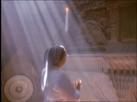 vídeos de stock e filmes b-roll de slow motion tilt down of catholic nun praying at altar in church / east java / indonesia / god rays - catolicismo