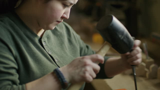 slow motion tilt down on woman chiseling wood in workshop / provo, utah, united states - provo video stock e b–roll